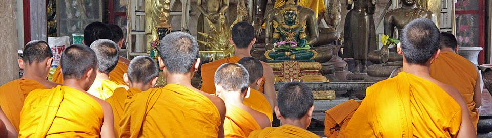 monks praying in front of a copy of the Emerald Buddha
