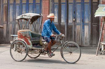 man pedaling rickshaw