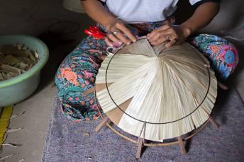 woman making bamboo hat