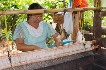 woman sitting at silk-weaving loom
