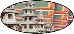 chinese stone towers in front of colorful temple roof