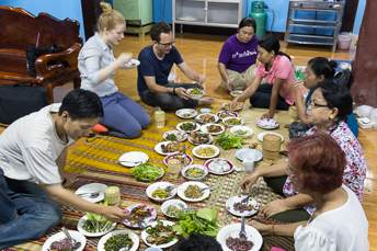 people eating Isan food while sitting on the floor