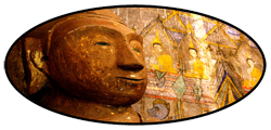 old Buddha head in front of murals
