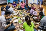 group of people eating meal while sitting on floor