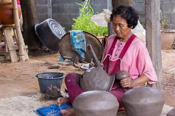 woman making a clay pot using a paddle