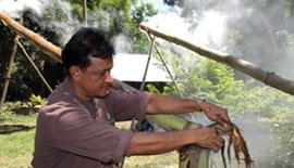 man starting fire at end of bamboo tube