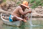 man in a boat fishing with a net