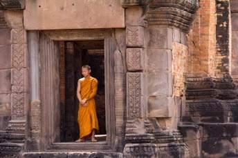 monk standing in doorway of Khmer ruin