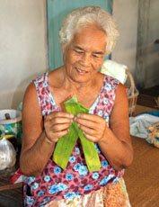 woman folding banana leaves