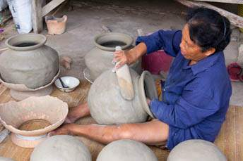 woman making pottery with a paddle