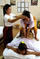 woman teaching two Thai massage students
