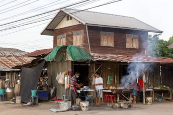 people grilling meat in front of a wooden house