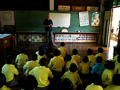 man teaching English to young students