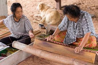 woman weaving a sitting mat