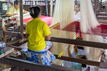 four women working on a giat loom